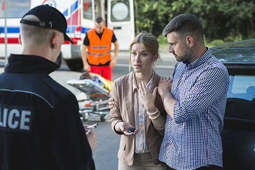 Young couple talk to police officer after crash